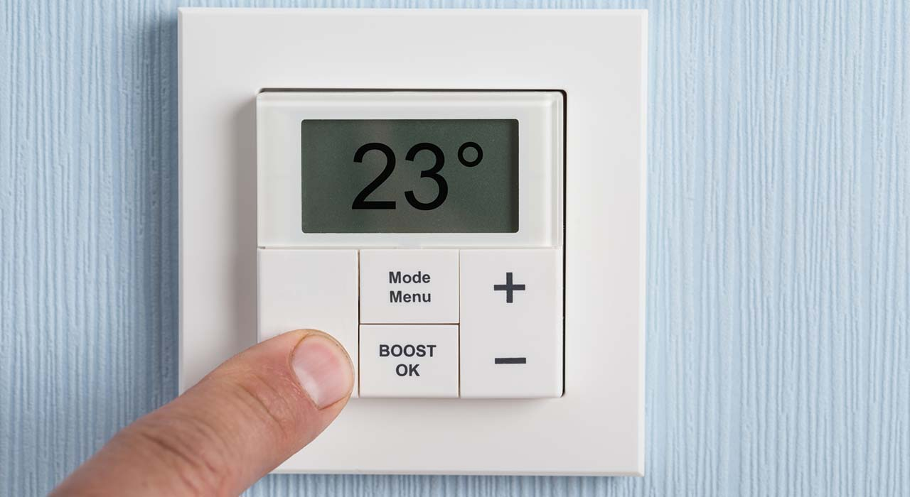 Person Adjusting Temperature Of Thermostat